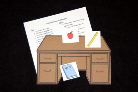 Following directions with prepositions using a desk, apple, rule, and book.